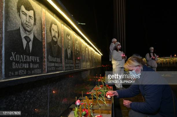 Woman wearing a face mask lights candles at the monument to Chernobyl victims in Slavutich, the city where the power station's personnel lived, some...
