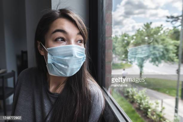 woman wearing a face mask looking out of a window during lockdown - depression sadness stock pictures, royalty-free photos & images