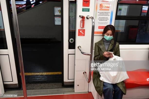 A woman wearing a face mask looks at her mobile as she sits in an empty metro carriage on February 28 in the northern city of Milan Italy urged...