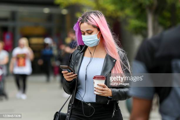 Woman wearing a face mask looks at her mobile phone.