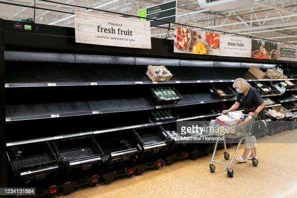 Woman wearing a face mask near empty fruit and veg shelves in an ASDA store on July 23, 2021 in Cardiff, United Kingdom. Supermarkets across the UK...