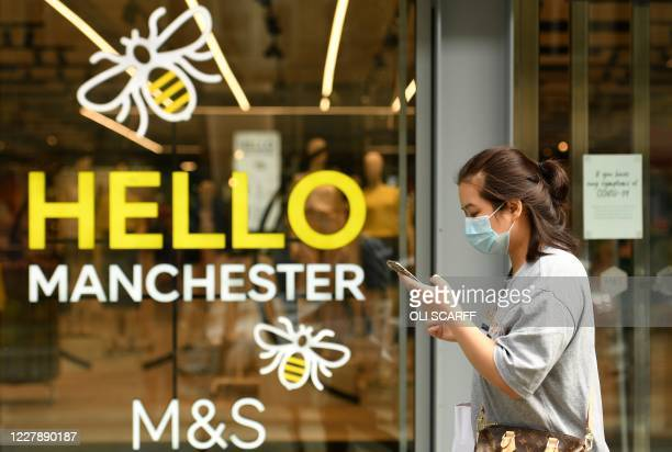 A woman wearing a face mask or covering due to the COVID19 pandemic walks past a Marks Spencer store in Manchester northwest England on August 3...