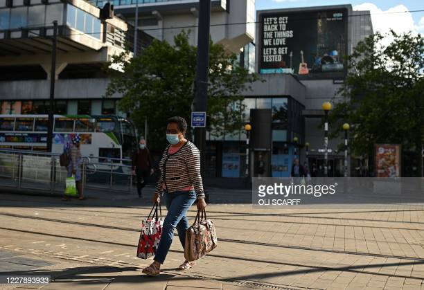 A woman wearing a face mask or covering due to the COVID19 pandemic walks near a sign urging people to 'get tested' to see if they have coronavirus...