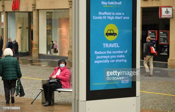 Woman wearing a face mask or covering due to the COVID-19 pandemic, sits on a bench close to a display showing health advice in the shopping district...