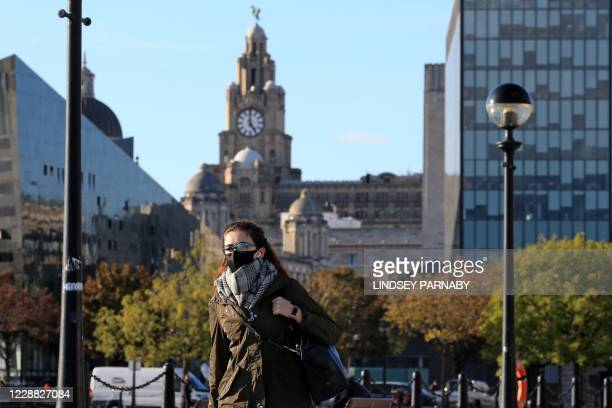 Woman wearing a face mask or covering due to the COVID-19 pandemic, walks near the Liver Building in Liverpool, north west England on October 1 as...