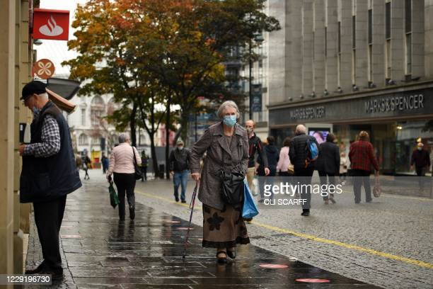 Woman wearing a face mask or covering due to the COVID-19 pandemic, walks along the pavement in the shopping district in central Sheffield, south...
