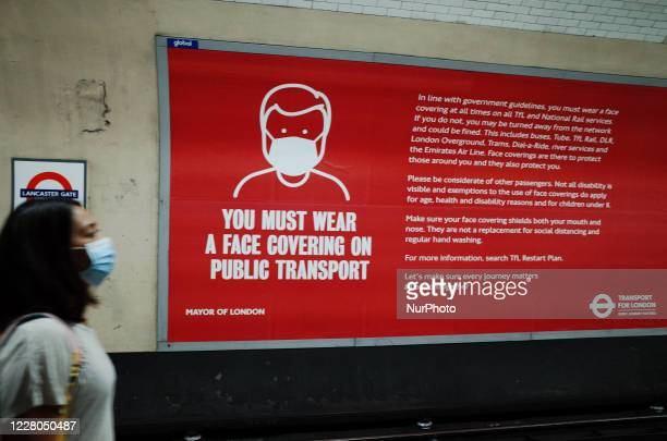 Woman wearing a face mask passes a poster reminding passengers of the need for face coverings on public transport at Lancaster Gate station on the...