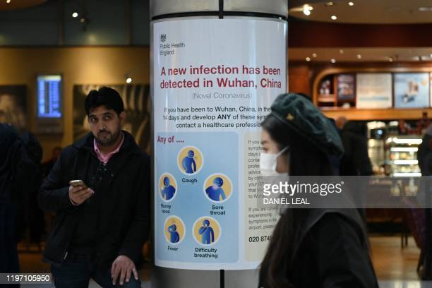 A woman wearing a face mask passes a Public Health England sign warning arriving passengers that a virus Coronavirus has been detected in Wuhan in...