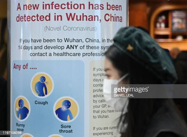 A woman wearing a face mask passes a Public Health England sign warning passengers arriving on flights into the UK that a virus Coronavirus has been...