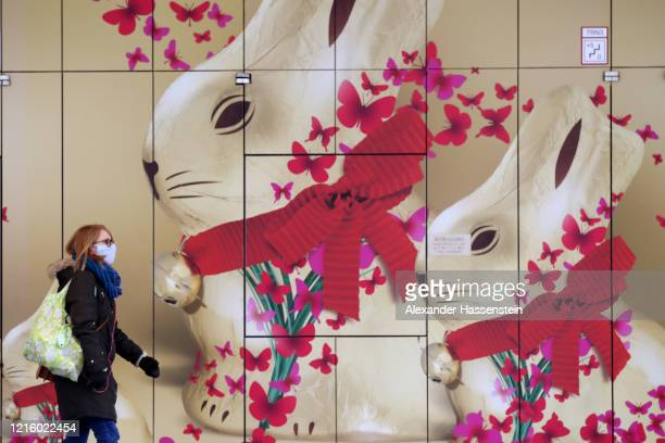 A woman wearing a face mask passes a showcase window with Easter bunnies pictured on March 31 2020 in Downtown Munich Germany COVID19 is having a...