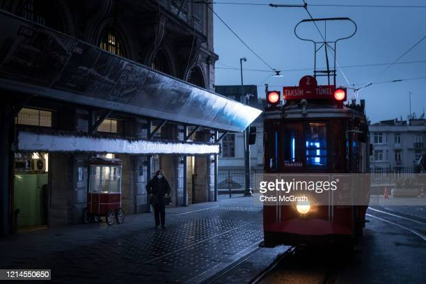 A woman wearing a face mask passes the famous Istiklal street red tram parked at the end of a street on March 23 2020 in Istanbul Turkey Turkey has...