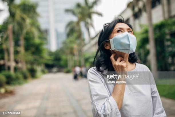 vrouw die een gezichtsmasker draagt - epidemic stockfoto's en -beelden