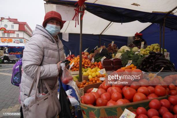 Woman wearing a face mask purchases tomatoes at a street market, on November 12, 2020 in Dedovsk, 18 km. West of Moscow, Russia. The requirement to...