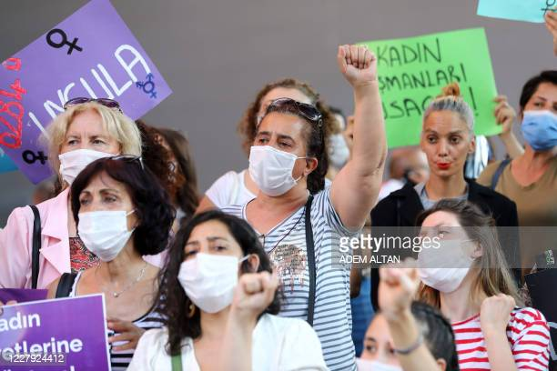 Woman wearing a face mask raises her fist in Ankara, on August 5 during a demonstration to demand the government does not withdraw from the Istanbul...