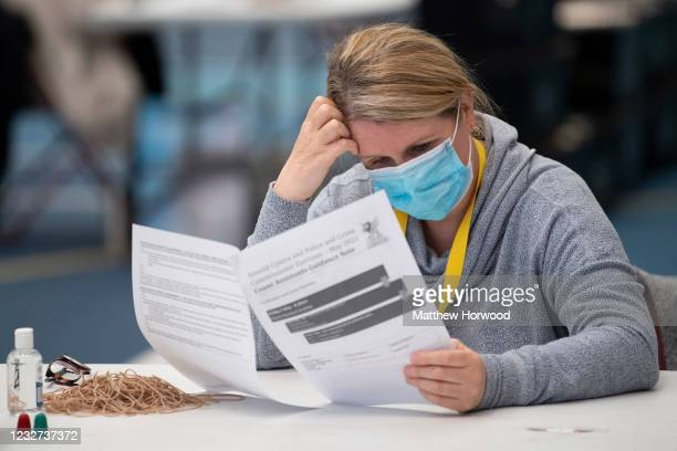 Woman wearing a face mask reads guidelines ahead of counting for the Senedd election at the Cardiff House of Sport on May 7, 2021 in Cardiff, Wales....