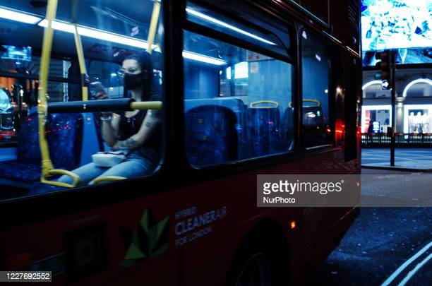 Woman wearing a face mask rides a bus through Piccadilly Circus late at night in London, England, on July 18, 2020. London's emergence from...