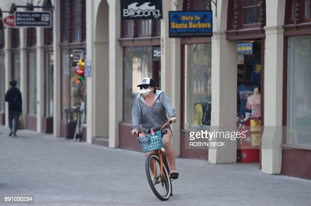 TOPSHOT A woman wearing a face mask rides her bike on State Street the main shopping street in Santa Barbara California December 12 2017 The Thomas...