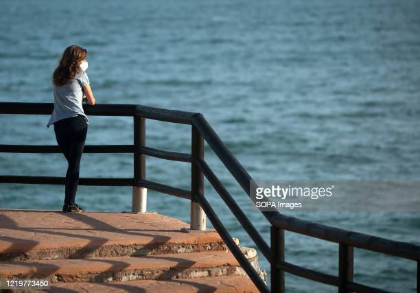 A woman wearing a face mask seen at El Cantal cliffs on a sunny day amid easing of restrictions caused by COVID19 outbreak Most cities in Spain are...