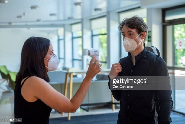 A woman wearing a face mask shows a musician from the Basque Symphony Orchestra his temperature reading on May 28 2020 in San Sebastian Spain All...