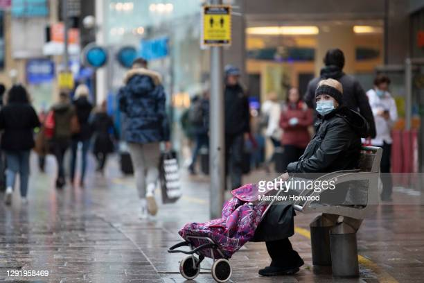 Woman wearing a face mask sits on a bench alone on December 18 in Cardiff, Wales. A two-household limit will be in place from December 23 to December...