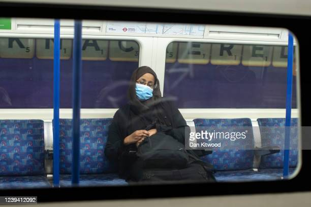 Woman wearing a face mask sleeps on the underground under a sign that reads 'Knackered' on June 01, 2020 in London, England. The British government...