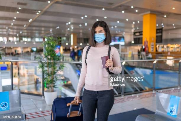 a woman wearing a face mask standing in an empty airport - government shutdown stock pictures, royalty-free photos & images