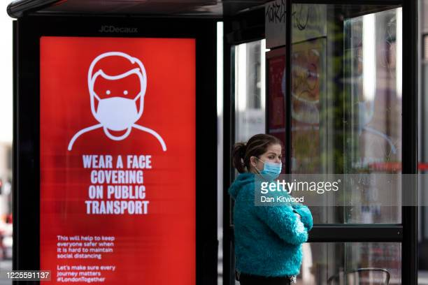 A woman wearing a face mask stands at a bus stop next to a sign about wearing face masks on public transport on May 18 2020 in London England The...