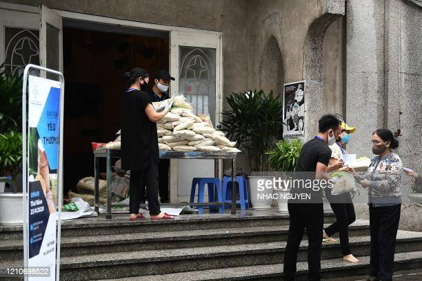 A woman wearing a face mask stands in a queue for free rice at the Hanoi Evangelical Church on April 23 as Vietnam eased its nationwide social...