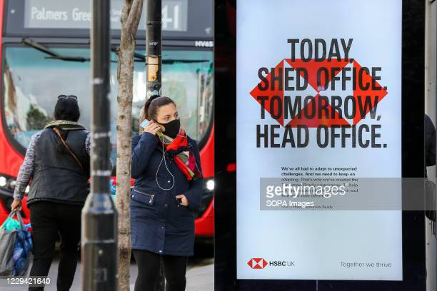 Woman wearing a face mask stands next to a HSBC advert at a bus stop in London.