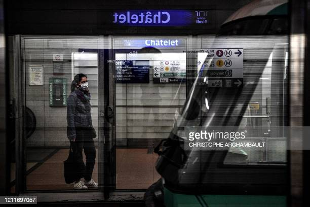 A woman wearing a face mask stands on a metro platform as she waits to board a train at Chatelet station in Paris on May 4 2020 on the 49th day of a...
