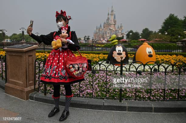 TOPSHOT A woman wearing a face mask takes a selfie while visiting the Disneyland amusement park in Shanghai on May 11 2020 Disneyland Shanghai...