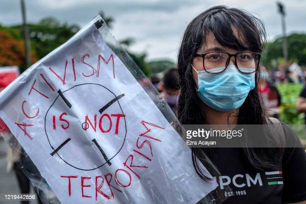Woman wearing a face mask takes part in a protest against President Duterte's Anti-Terror bill on June 12, 2020 in Quezon city, Metro Manila,...
