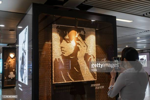 Woman wearing a face mask takes photos of a portrait of singer Jay Chou, which is made up of Oreo Cookies, during an Oreo Art Exhibition at Xujiahui...