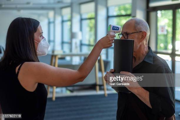 A woman wearing a face mask takes the temperature of a musician from the Basque Symphony Orchestra as he covers his mouth with a folder on May 28...