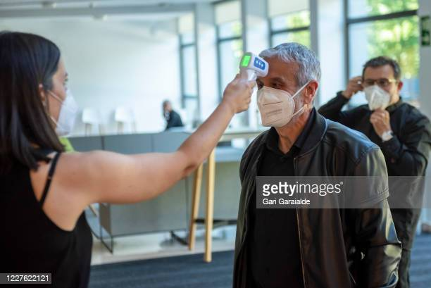 A woman wearing a face mask takes the temperature of a musician from the Basque Symphony Orchestra on May 28 2020 in San Sebastian Spain All regions...