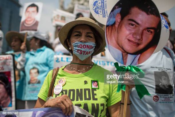 A woman wearing a face mask that reads 'Where are they' shows a sign with the image of his missing son during a march on Mother's Day on May 10 2017...