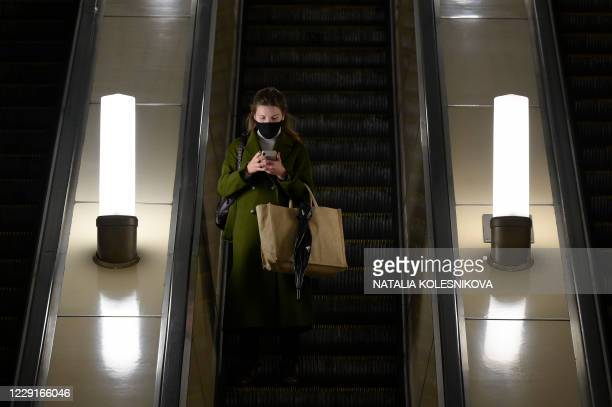 Woman wearing a face mask to protect against the coronavirus disease uses her smartphone while riding an escalator at a metro station in Moscow on...
