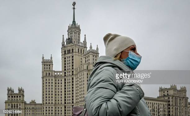 Woman wearing a face mask to protect against the coronavirus disease walks along a bridge near a Stalin-era skyscraper in central Moscow on October...