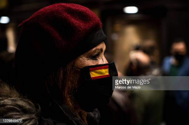 Woman wearing a face mask to protect against the spread of coronavirus with a Spanish flag protesting against censorship in Social Networks in front...
