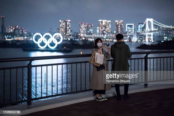 Woman wearing a face mask uses a smartphone as she takes a photograph in front of the Olympic rings at night on February 26, 2020 in Tokyo, Japan....