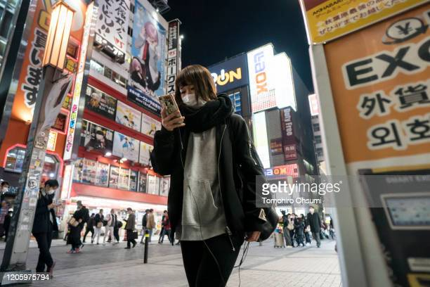 A woman wearing a face mask uses a smartphone as she walks through a shopping district at night on February 13 2020 in Tokyo Japan At least 219...