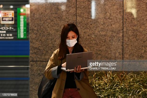 A woman wearing a face mask uses her computer at the end of the work day in Tokyo on March 13 2020 As of March 13 there were over 140000 confirmed...