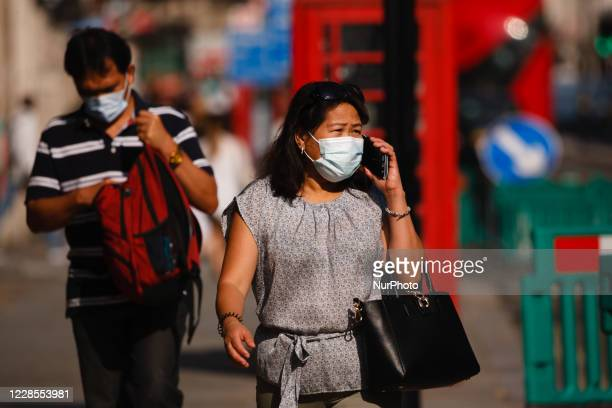 Woman wearing a face mask uses her phone on Piccadilly in London, England, on September 16, 2020. While the UK continues to edge towards economic...