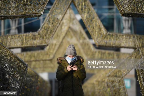 Woman wearing a face mask uses her smartphone walking through star shaped festive decorations set for the upcoming New Year and Christmas holidays...