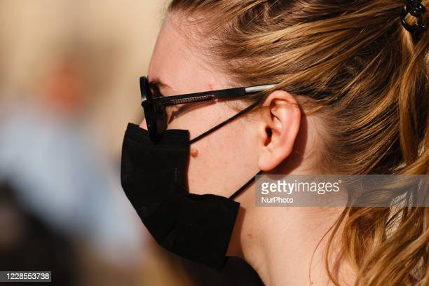 A woman wearing a face mask waits at a pedestrian crossing in Piccadilly Circus in London England on September 16 2020 While the UK continues to edge...