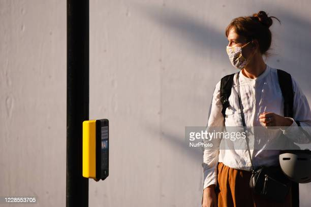 Woman wearing a face mask waits at a pedestrian crossing on Oxford Street in London, England, on September 16, 2020. While the UK continues to edge...