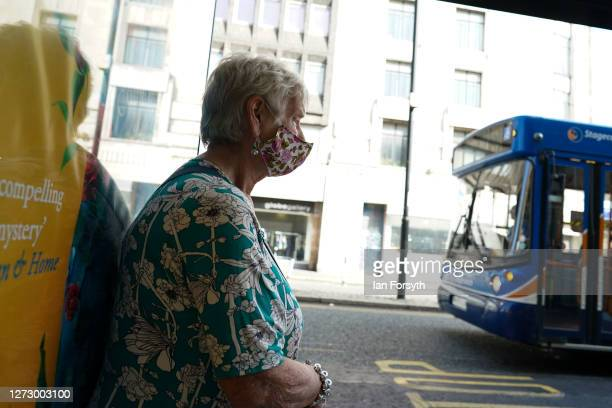A woman wearing a face mask waits for a bus in Newcastle on September 17 2020 in Newcastle upon Tyne England Almost two million people in northeast...
