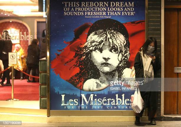 "Woman wearing a face mask waits for an evening show of ""Les Miserables"" at Queen's Theatre on March 12, 2020 in the theatres and restaurants district..."