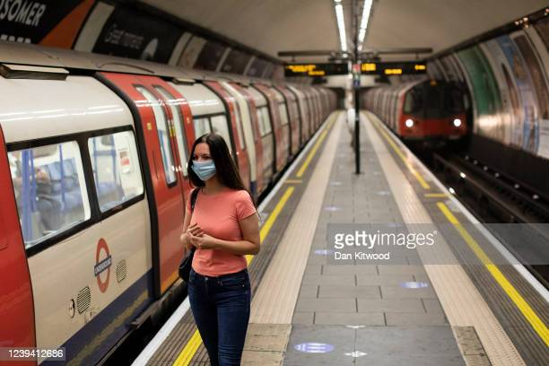 Woman wearing a face mask waits to board a train at Clapham Common underground on June 01, 2020 in London, England. The British government further...