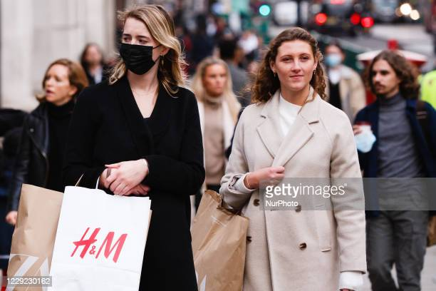Woman wearing a face mask waits with bags of clothes shopping at a pedestrian crossing on Regent Street in London, England, on October 22, 2020....